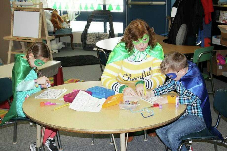 Bad Axe Elementary students celebrated all things '100' this week in conjunction with the school's 100th day. From left, Olivia Smith glues on one of the final pieces to her puzzle as Sonja Cady (center) gives Carter Prill a hand with his. Throughout the day on Tuesday, students worked on projects and played games that incorporated the number 100. The superhero theme was inspired by the popular children's book, 'Zero to Hero.' (Bradley Massman/Huron Daily Tribune)
