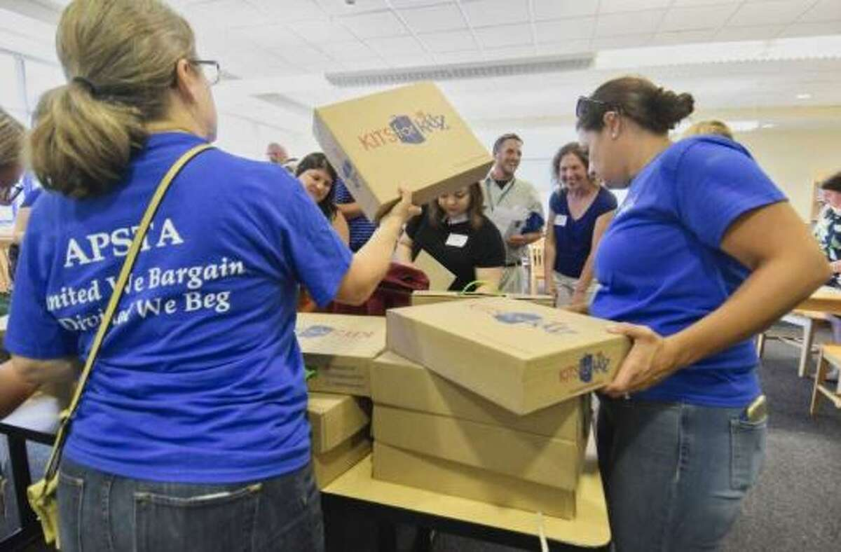 Members of the Albany Public School Teachers Association hand out free book bags and school supplies to new teachers in the Albany School District on Monday, Aug. 27, 2018, in Albany, N.Y