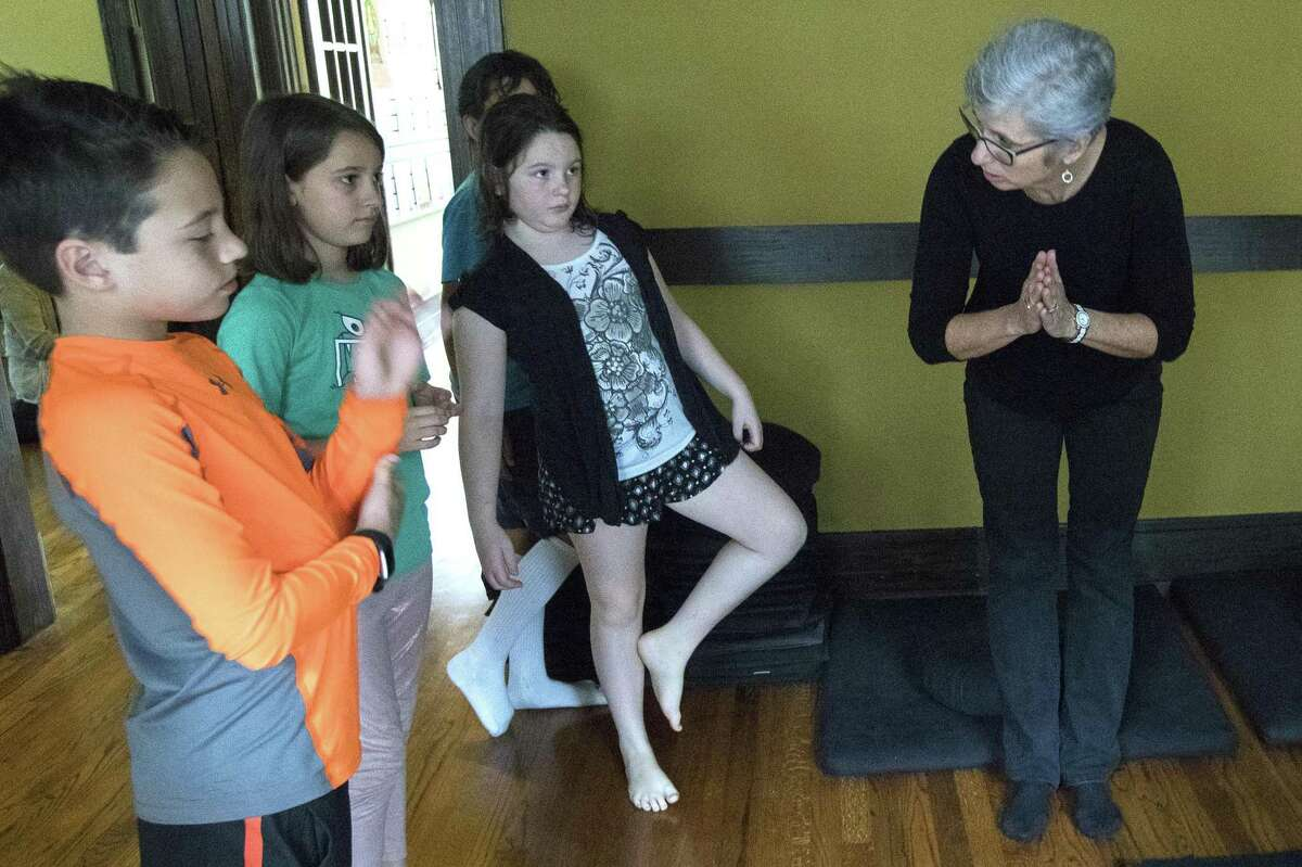Sally Muñoz leads her students in a bow as they enter a meditation area during Mindfulness for Children: Notice what is happening right now, in this moment! class, at the Houston Zen Center on Saturday, Feb. 23, 2019, in Houston. The class is aimed at second, third and fourth grade children, learning how to be present, how to focus on the moment how to continue practicing the skills at home.