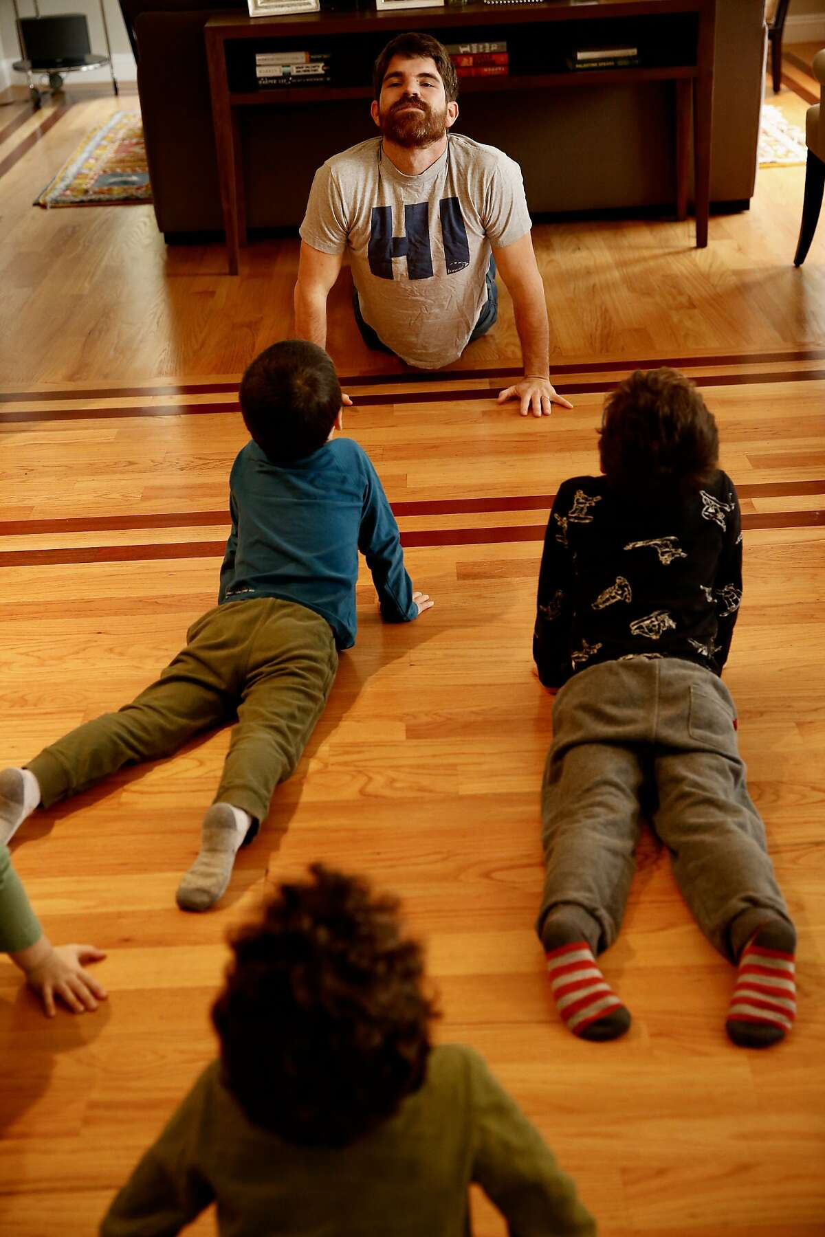 Darrow Deluca leads students from Kaiser Elementary School, Melrose Leadership Academy, and Claremont Middle School in a yoga pose in Alicia Johnson's home in Berkeley, Calif., on Wednesday, February 27, 2019. Johnson, 38, is a stay at home mother, who wants to make sure that those who want to support the teachers and not cross the picket line but have to work have options for childcare during the Oakland Teacher's Strike.