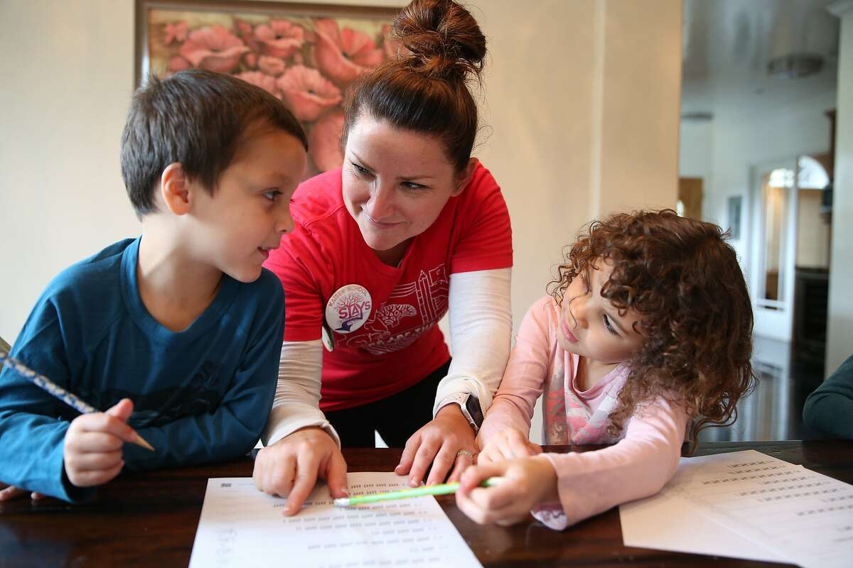 Alicia Johnson helps Gage Hernandez (left), 6, and her daughter, Grace Johnson, 6, kindergarteners at Kaiser Elementary School, with a counting assignment inside Johnson's home in Berkeley, Calif., on Wednesday, February 27, 2019. Johnson, 38, is a stay at home mother, who wants to make sure that those who want to support the teachers and not cross the picket line but have to work have options for childcare during the Oakland Teacher's Strike.