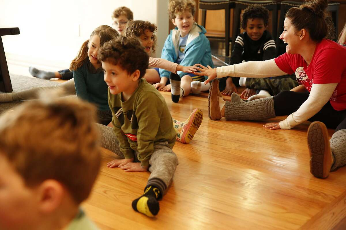 Alicia Johnson (right) stretches with students as she hosts them at her home in Berkeley, Calif., on Wednesday, February 27, 2019. Johnson, 38, is a stay at home mother who wants to make sure that those who want to support the teachers and not cross the picket line but have to work have options for childcare during the Oakland Teacher's Strike.