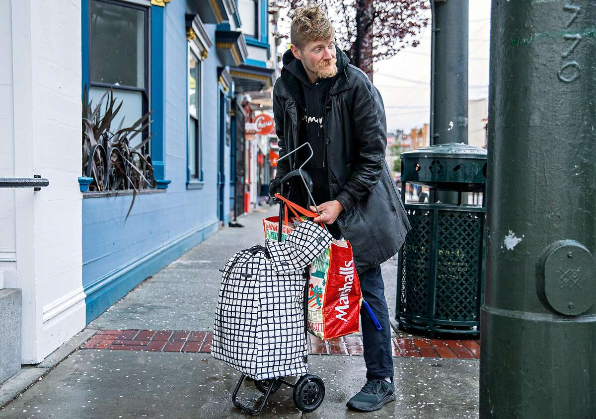 John Constantine, 39, cleans up his area after sleeping in a storefront near 14th Street along Market Street in San Francisco, Calif. Wednesday, Feb. 27, 2019.