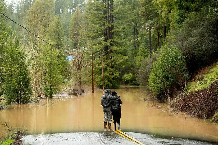 Ari and Lea Herman hug while watching water flood over Highway 116 east of Mays Canyon Road in Guerneville on Wednesday. Photo: Noah Berger / Special To The Chronicle