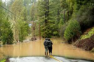 Ari Herman and wife Lea Herman hug while watching water flood over Highway 116 east of Mays Canyon Rd. in Guerneville, Calif., on Wednesday, Feb. 27, 2019.