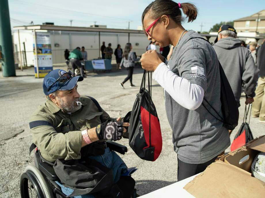 Robert Lopez, Navy veteran from Vietnam era, receives a free frozen turkey from volunteer and Army veteran herself Delores Rawls, who served during Operation Iraqi Freedom, during a 2018 event. Many veterans face also face legal issues — and legal aid is available to them. Photo: Matthew Busch /For The San Antonio Express-News / © Matthew Busch