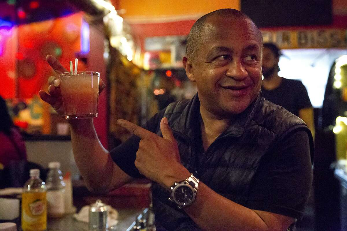 Marco Senghor, owner of Bissap Baobab, mixes drinks for customers at his restaurant in 2018. Senghor recently transformed his Oakland restaurant into a collective selling goods from several vendors.