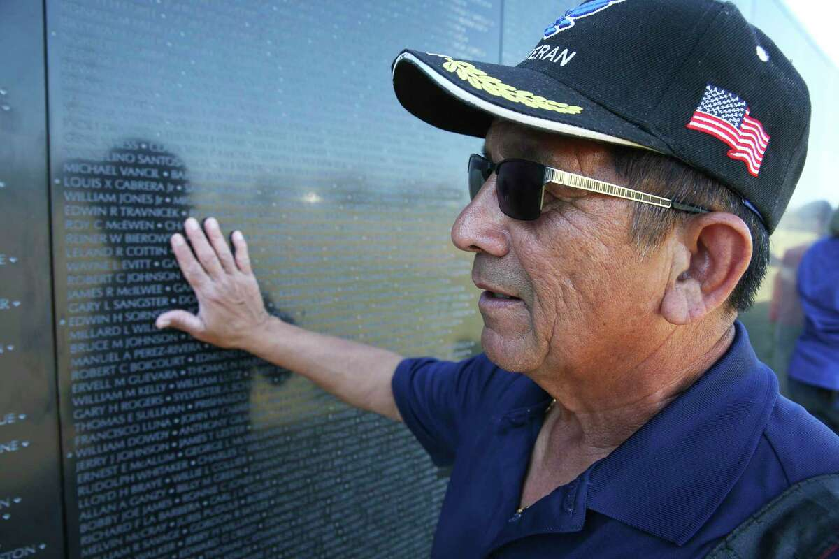 """Vietnam veteran Martin Cavazos immediately becomes emotional as he touches """"The Wall That Heals,"""" a traveling Vietnam Memorial Wall replica assembled at Fort Sam Houston National Cemetery last February. Cavazos was a combat photographer in the war. A series of Veterans Day events are planned this weekend and Monday in the area."""