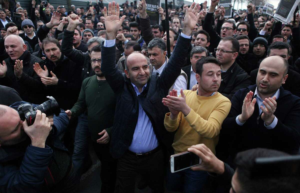Abdulhamit Bilici, editor-in chief of Zaman newspaper, salutes people gathered in support outside the headquarters of Zaman in Istanbul, Saturday, March 5, 2016. The European Union is facing increasing pressure to speak out against the erosion of media freedom in Turkey following the takeover of the country's largest-circulation newspaper, but few expect it to take a bold stance toward Ankara while trying to assure its help in dealing with the migration crisis. Police used tear gas and water cannons for a second day running on Saturday to disperse hundreds of protesters who gathered outside the headquarters of Zaman newspaper - now surrounded by police fences. (AP Photo)