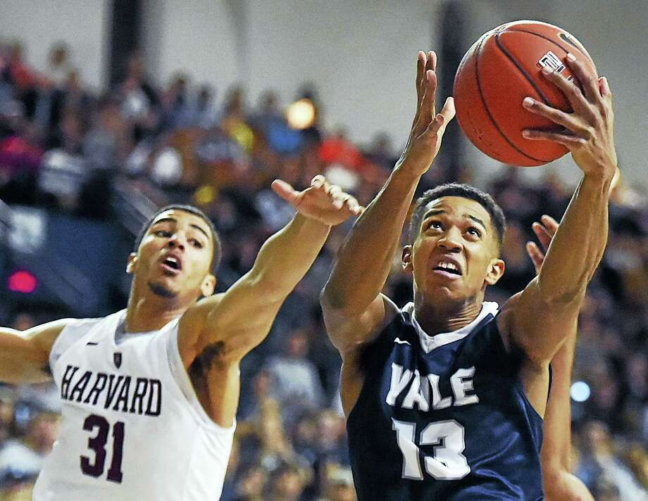 Yale guard Trey Phills elevates in the paint as Harvard freshman forward Seth Towns defends on Feb. 11, 2017. Photo: Catherine Avalone / Catherine Avalone /New Haven... / Catherine Avalone/New Haven Register