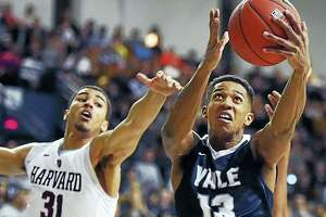 Yale guard Trey Phills elevates in the paint as Harvard freshman forward Seth Towns defends on Feb. 11, 2017.