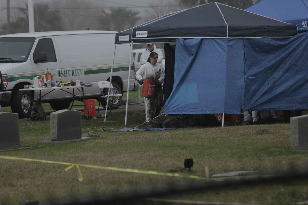 A member of the Galveston County Sheriff's Crime Scene Unit removes dirt while excavating an area at the San Leon Cemetery looking for evidence in a cold case on Wednesday, Feb. 27, 2019.