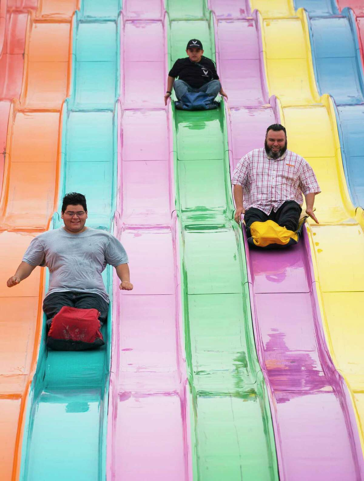 (LtoR) Dylan Eves, 16, Liam Eves, 8, and James Eves slide down the giant slides at the carnival of the Houston Livestock Show and Rodeo, Wednesday, Feb. 27, 2019 in Houston.