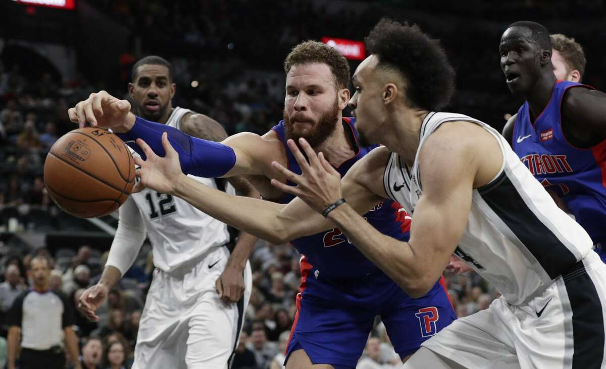 Detroit Pistons forward Blake Griffin, center, and San Antonio Spurs guard Derrick White, right, reach for the ball during the first half of an NBA basketball game in San Antonio, Wednesday, Feb. 27, 2019. (AP Photo/Eric Gay)