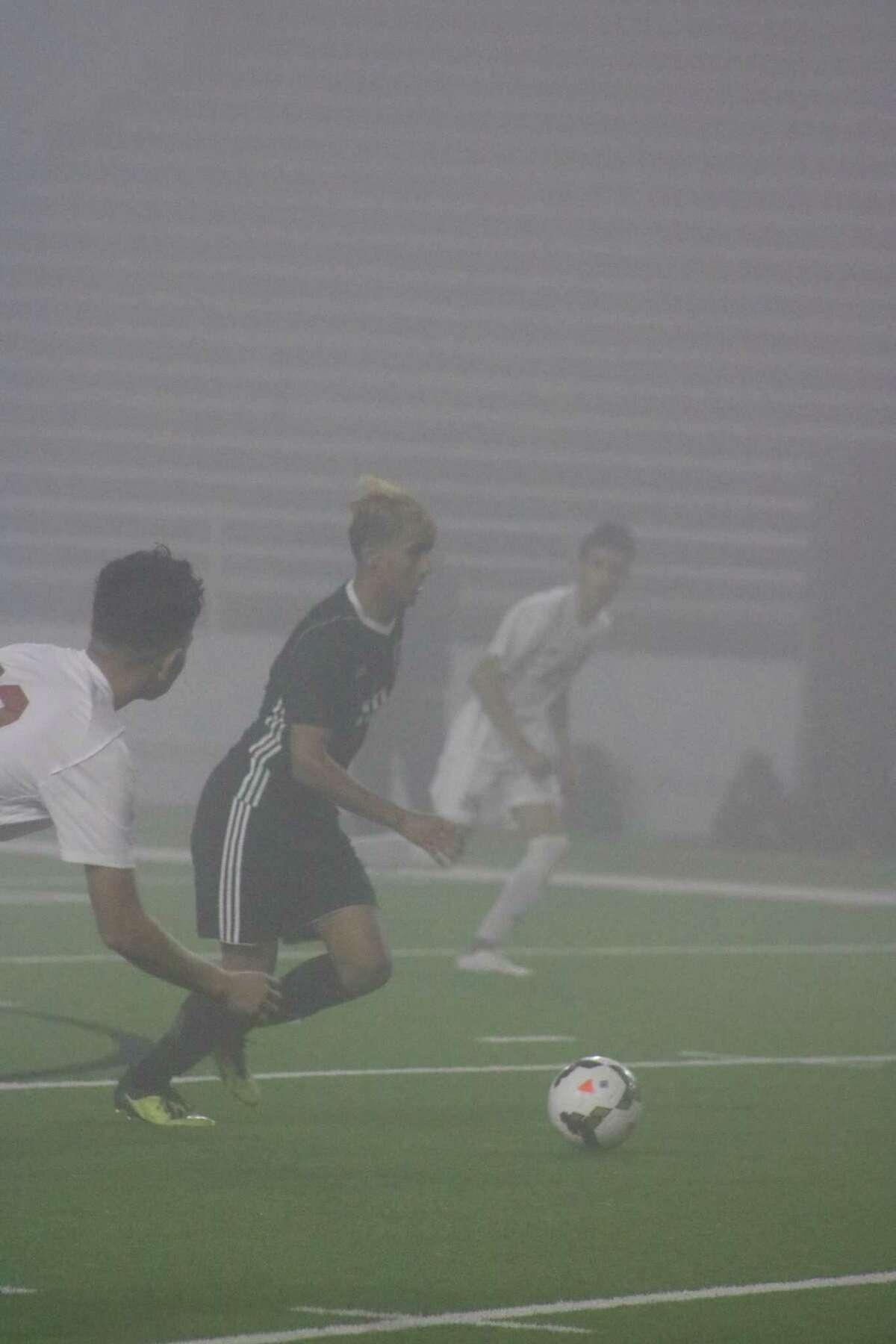 Amidst Wednesday night's dense fog at Veterans Memorial Stadium, a Pasadena player dribbles the ball towards Dobie's goal in second-half action.