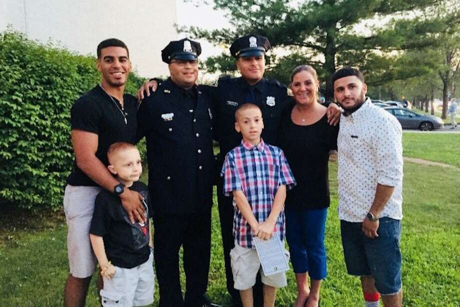 Norwalk police officer Phil Roselle and his son Justin Roselle, a New Haven police officer pose with the family after Justin's graduation in 2014. Left to right, Derek Edwards and Ryan Roselle, Phil, Justin, Michael Roselle Phil's wife Debbie and Richie Roselle. Photo: Contributed Photo / Contributed Photo / Connecticut Post Contributed