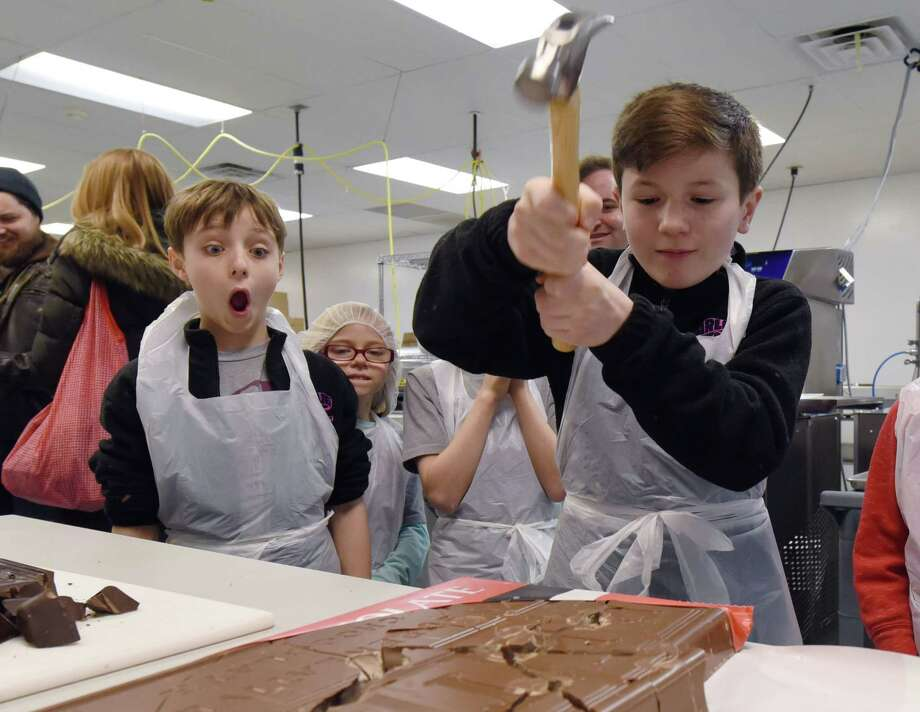 Collin Jeffrey, 12, breaks up a slab of chocolate with a hammer as Rueby Wood, 12, looks on during a tour of KrauseOs Homemade Candy on Wednesday, Feb. 27, 2019 at KrauseOs Homemade Candy in Albany, NY. (Phoebe Sheehan/Times Union) Photo: Phoebe Sheehan / 40046293A