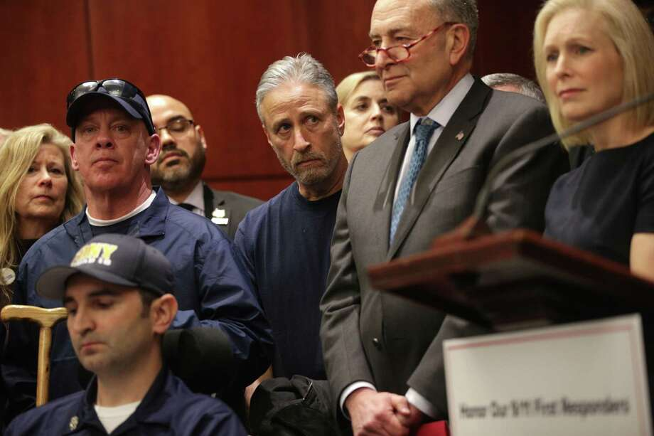 """WASHINGTON, DC - FEBRUARY 25: Comedian and advocate for 9/11 first responders Jon Stewart, U.S. Senate Minority Leader Sen. Chuck Schumer (D-NY) and Sen. Kirsten Gillibrand (D-NY) listen during a news conference February 25, 2019 on Capitol Hill in Washington, DC. Joined by 9/11 first responders, survivors and their families, Sen. Kirsten Gillibrand (D-NY) held a news conference to discuss the introduction of the bipartisan """"Never Forget the Heroes: Permanent Authorization of the September 11th Victim Compensation Fund Act"""" and to call for its swift passage. (Photo by Alex Wong/Getty Images) ***BESTPIX*** Photo: Alex Wong / Getty Images / 2019 Getty Images"""