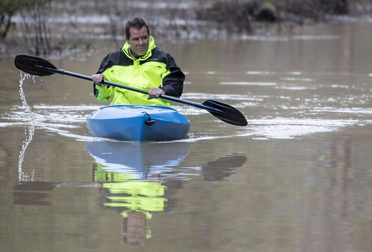 Guerneville resident Jeremiah Fox, 43, paddles in on a kayak after attempting to navigate high flood waters to check on his property along Highway 116 in Guerneville, Calif. Thursday, Feb. 28, 2019.