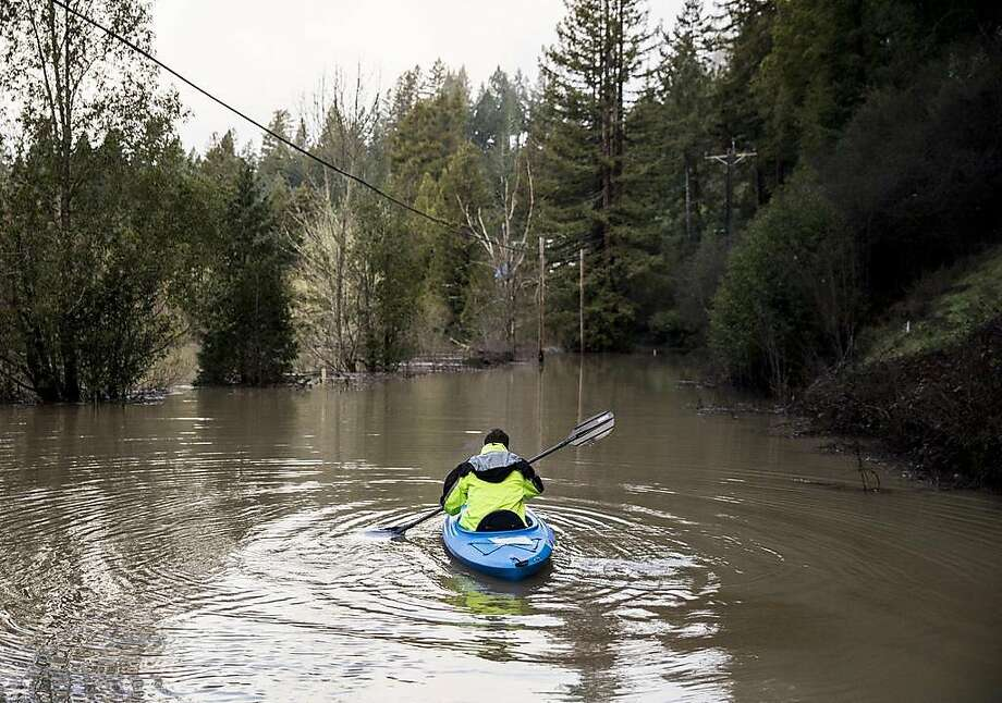 Guerneville resident Jeremiah Fox, 43, paddles out on a kayak as he attempts to navigate through high flood waters to check on his property along Highway 116 in Guerneville, Calif. Thursday, Feb. 28, 2019. Photo: Jessica Christian / The Chronicle