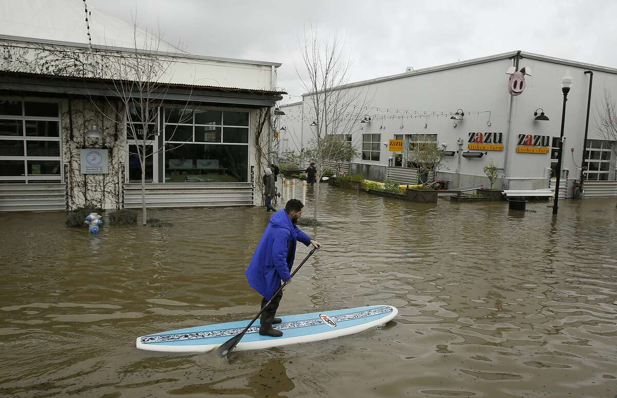 A man uses a paddle board to make his way through the flooded Barlow Market District on Feb. 27, 2019, in Sebastopol, Calif.