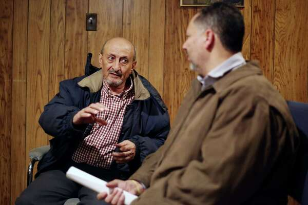 Jalal Abdulla, who has been waiting for a year and half for his wife to join him in the U.S. because of the travel ban, shares his story with Nabeel Shohatee, the owner of Marhaba Services in Schenectady. (Phoebe Sheehan/Times Union)