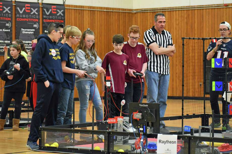 Weston Middle School students from two robotics teams compete at the New England Regionals in Worcester, Mass., on Feb. 23. Weston Middle School students are in the blue shirt with gold colored letters. Photo: Contributed