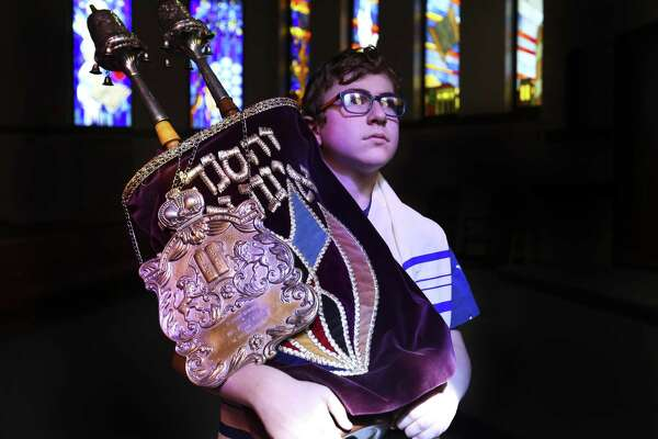 Aaron Rubin, 13, poses for a photograph with a restored vintage Torah at Congregation Shaar Hashalom on Sunday, Jan. 13, 2019, in Houston. Aaron will be the next person reading this Torah at his Bat Mitzvah in March. The smallest of four Torahs at the congregation was most likely from the WW II era and the letters were starting to fade, threatening the scroll until a local scribe was discovered. The restoration was completed in December.