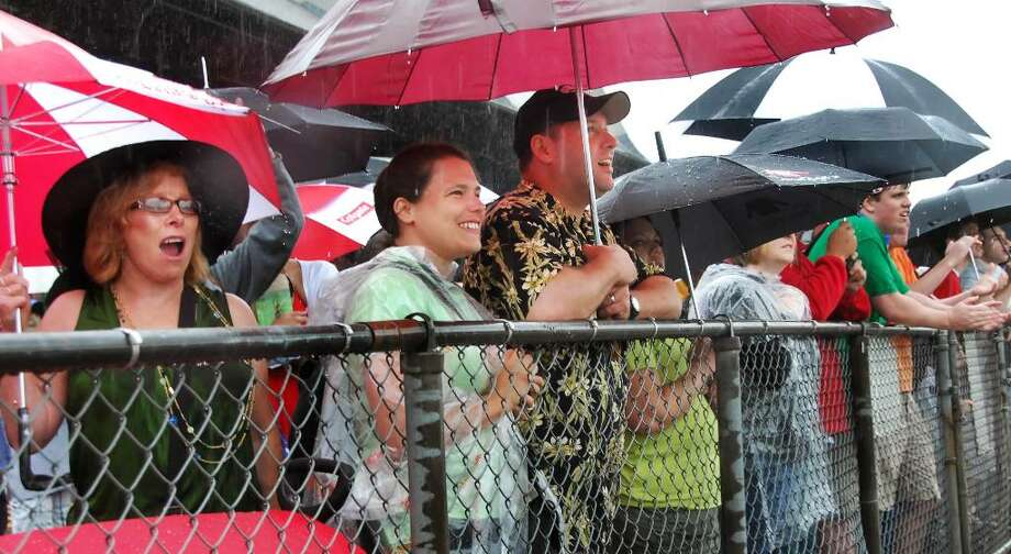 Rail birds, from left, Mary Anne Syden of Loudonville and Anne Halsey and Robert McKeon, both of Germantown,Md., brave heavy rains to cheer on the first race of the first day of the 2010 meet at Saratoga Race Course Friday morning July 23, 2010.   (John Carl D'Annibale / Times Union) Photo: John Carl D'Annibale / 00009600A