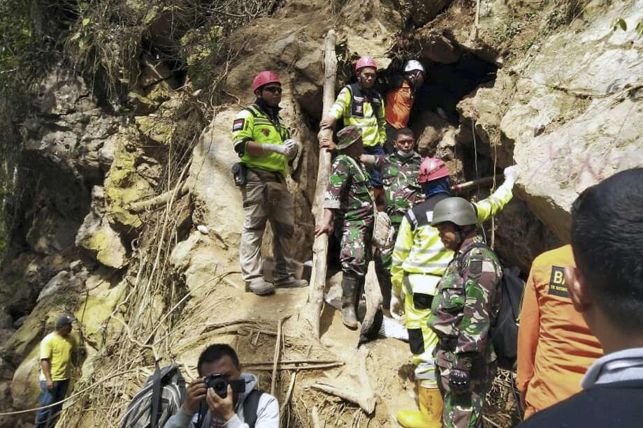 Rescuers stand at the entrance of a collapsed mine in Bolaang Mongondow, North Sulawesi, Indonesia. Photo: Associated Press