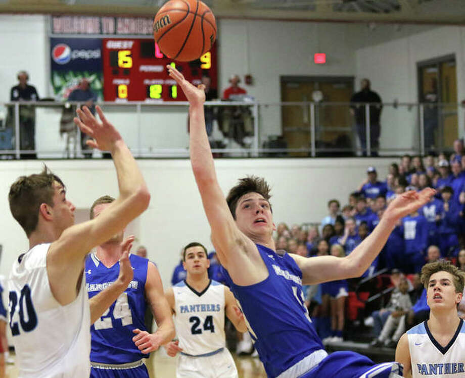 Marquette Catholic's Spencer Cox (middle) scores on an off-balance shot at the buzzer ending the first quarter as Pinckneyville's Grant Tanner (left) tries to contest the shot in Tuesday's semifinals at the Du Quoin Class 2A Sectional. Photo: Greg Shashack / The Telegraph