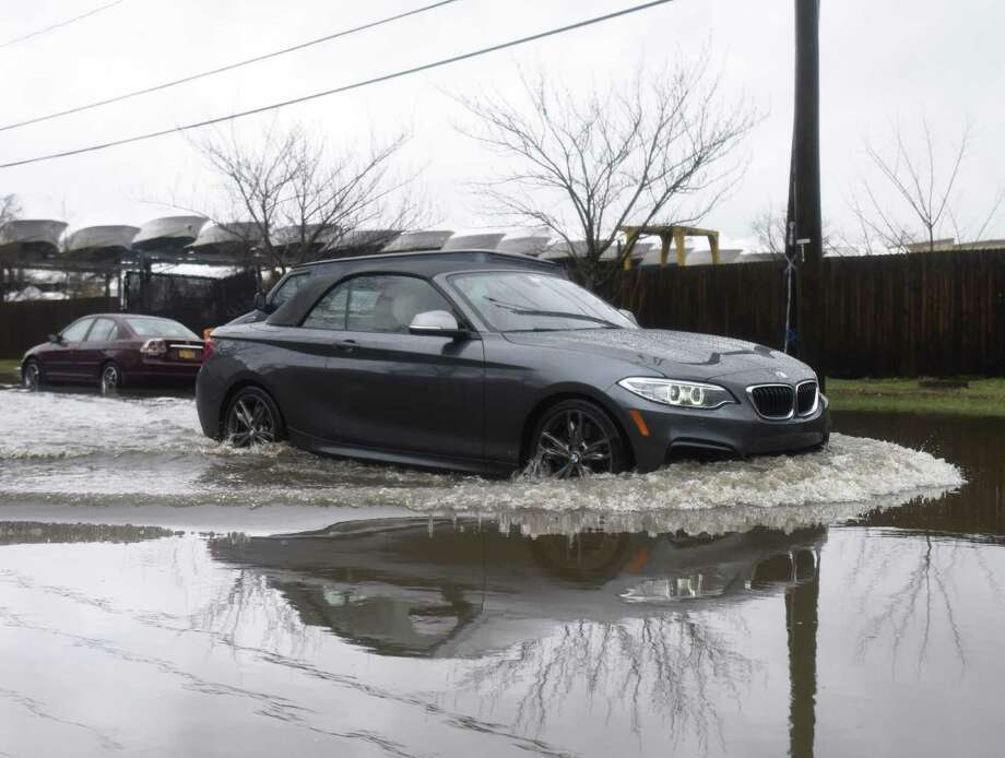 Traffic passes through a long, flooded stretch of North Water Street near the coastline in the Byram section of Greenwich, Conn. in April of 2018. Photo: Tyler Sizemore / Hearst Connecticut Media / Greenwich Time