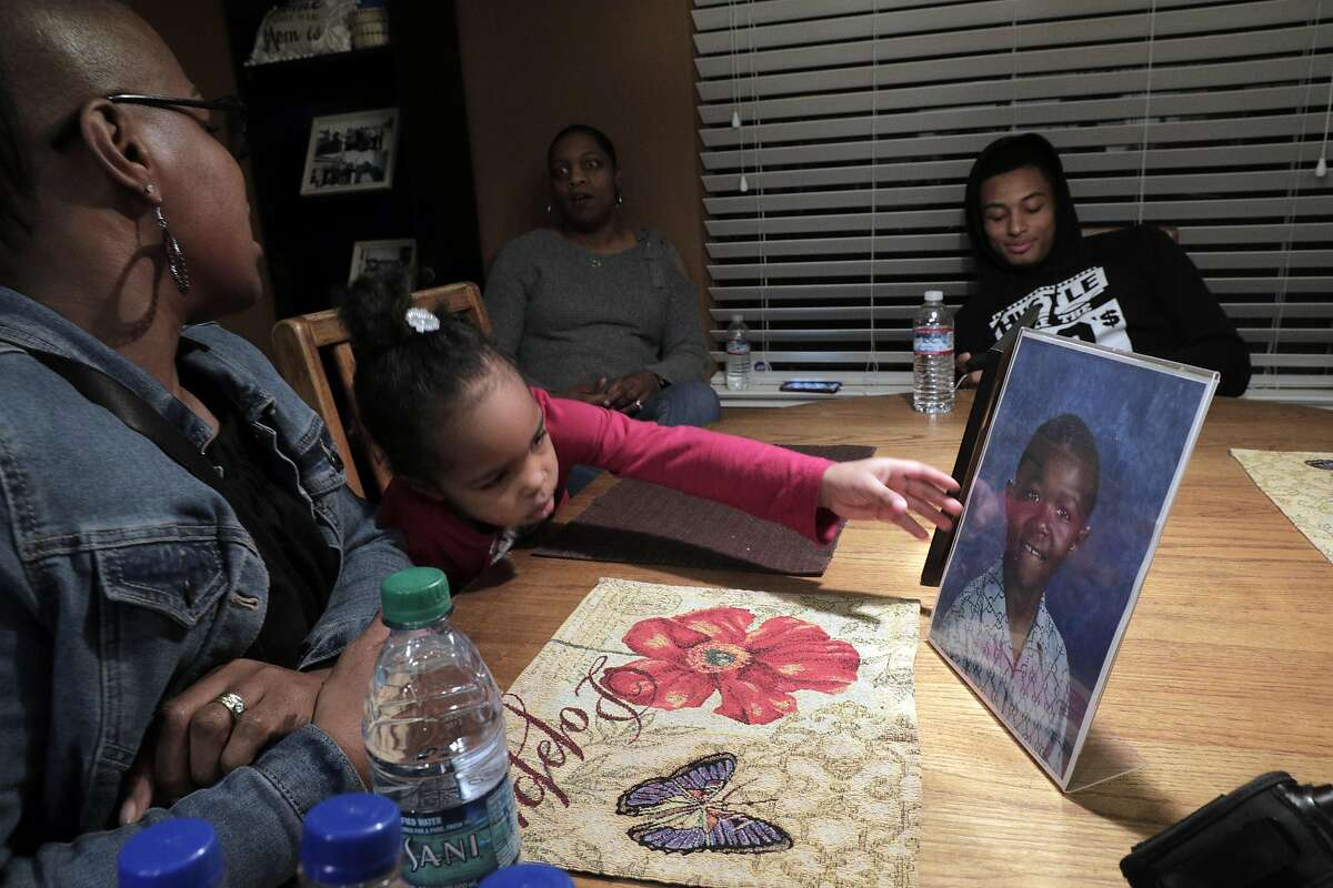 Peyton McCoy, 3, reaches for a photo of her uncle Willie McCoy, at the home of Kori McCoy in Hercules, Calif., on Thursday, February 14, 2019. The family of Willie McCoy, who was shot and killed by Vallejo Police officers as he woke up from sleeping in his car at a Taco Bell restaurant, gathered for press conference to address their issues with how their loved one was killed.