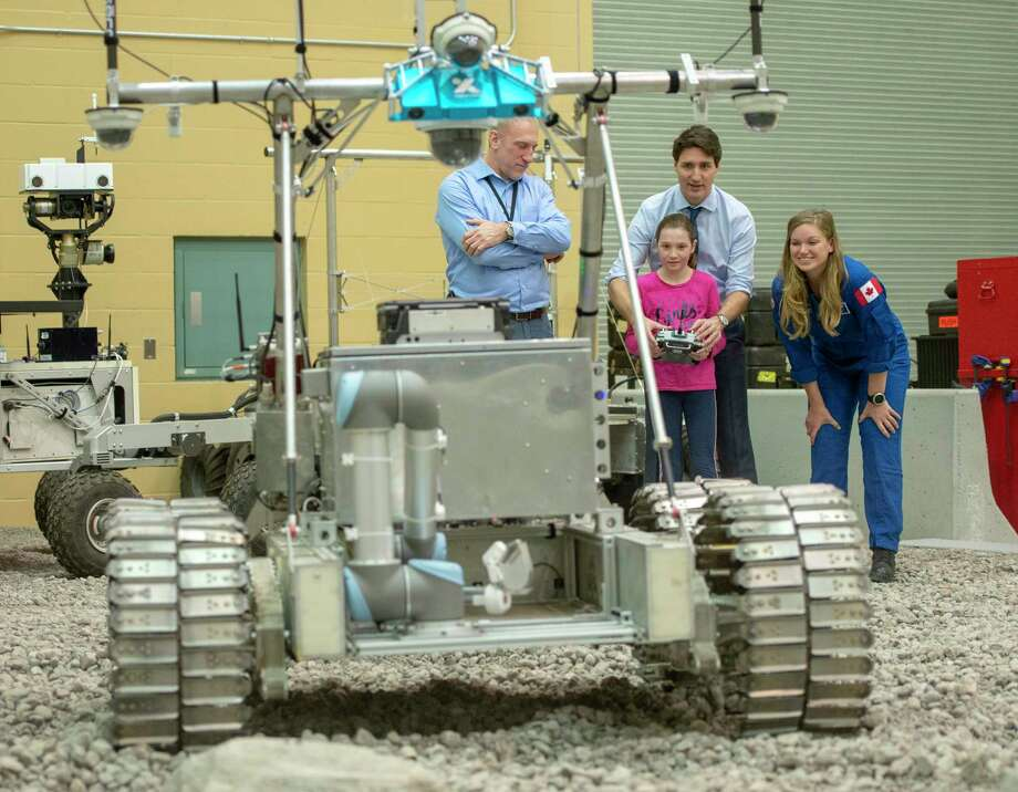 Canada's Prime Minister Justin Trudeau and his daughter, Ella-Grace, and astronaut Jenni Sidey-Gibbons drive a Juno six rover during a visit to the Canadian Space Agency headquarters , Thursday, Feb, 28, 2019 in St. Hubert, Quebec. Trudeau announced Thursday that Canada will take part in an international lunar space station project. (Ryan Remiorz/The Canadian Press via AP) Photo: Ryan Remiorz, Associated Press / The Canadian Press