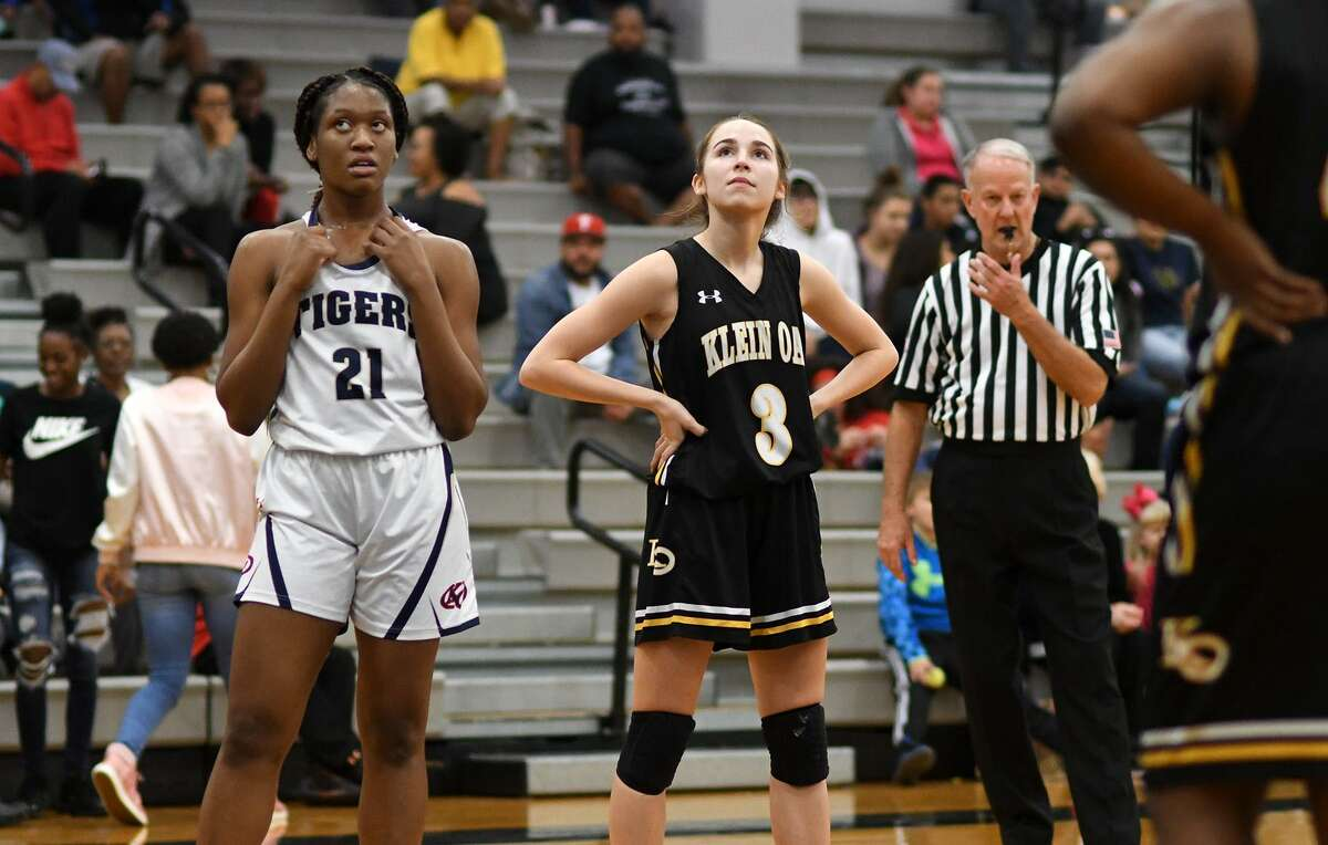 Klein Collins junior forward Ja'nyah Bennett (21) and Klein Oak junior guard Lane Rice (3) wait for free throws during the 2nd quarter of their District 15-6A matchup at Klein Collins High School on Jan. 18, 2019.