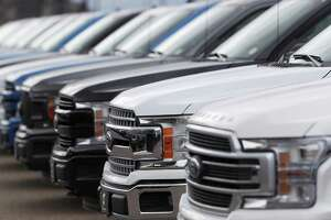 FILE--In this Sunday, Feb. 17, 2019, file photograph, a long row of unsold 2019 F150 pickup trucks sits at a Ford dealership in Broomfield, Colo. (AP Photo/David Zalubowski)