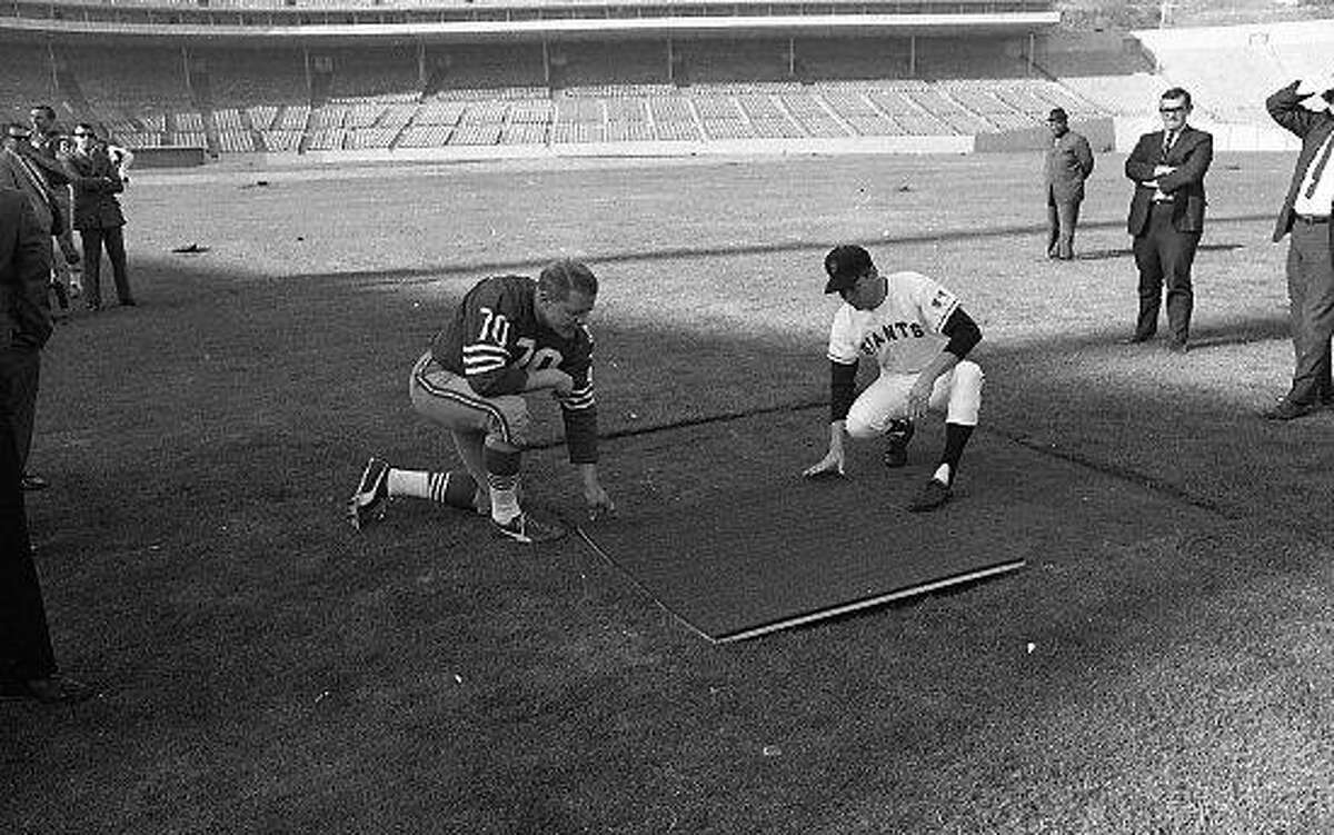 Giants and 49ers inspect installation of astroturf at Candlestick Park. 49er Charlie Krueger (70) and Giants second baseman Hal Lanier take a closer look. Photo ran 12/6/1969