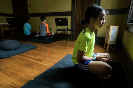 Karim Manasia meditates with his classmates during Mindfulness for Children: Notice what is happening right now, in this moment! class, at the Houston Zen Center on Saturday, Feb. 23, 2019, in Houston. The class is aimed at second, third and fourth grade children, learning how to be present, how to focus on the moment how to continue practicing the skills at home.