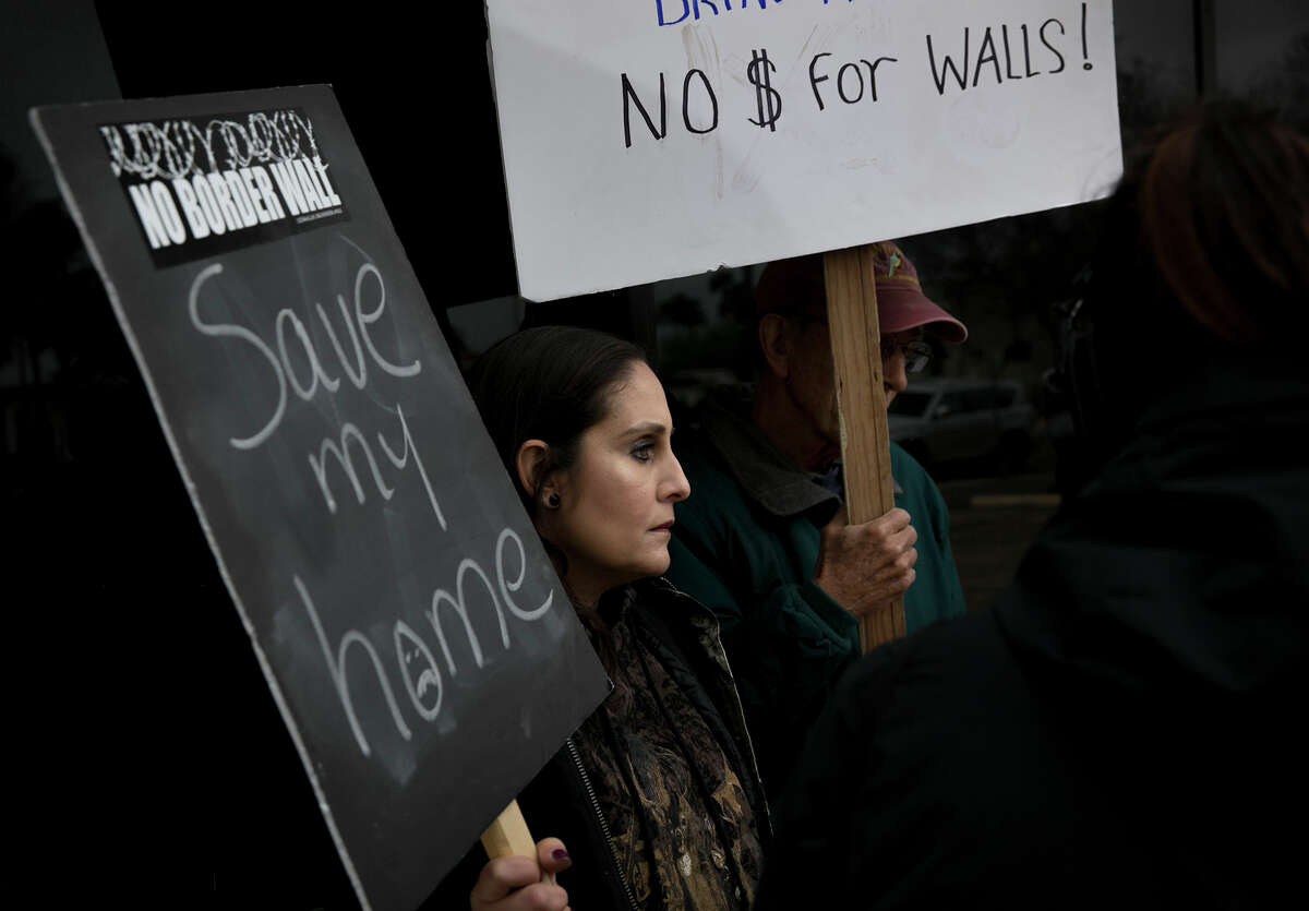 Nayda Alvarez of La Rosita, left, and Jim Chapman of Weslaco, along with a coalition of humanitarian, environmental and immigration rights activists, protest the border wall at the office of U.S. Rep. Henry Cuellar in Mission on Friday February 8, 2019. Alvarez' house is less than 100 yards from the Rio Grande and is in the path of a future section of the border wall.