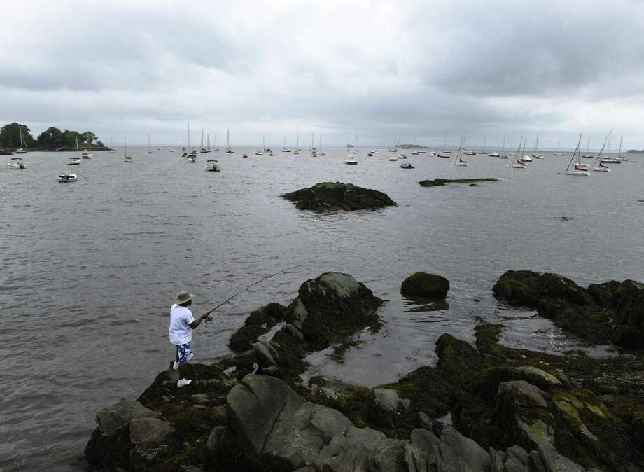 A man fishes at the end of Steamboat Road as storm clouds roll in overlooking Greenwich Harbor in Greenwich, Conn. Monday, July 22, 2018. Photo: Tyler Sizemore / Hearst Connecticut Media / Greenwich Time