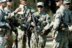 In this photo taken on Aug. 4, 2015, a female Army Ranger stands with her unit during Ranger School at Camp Rudder on Eglin Air Force Base, Fla. Since all military jobs are now open to women — including combat jobs — women should be required to register for the draft, a federal judge has ruled.