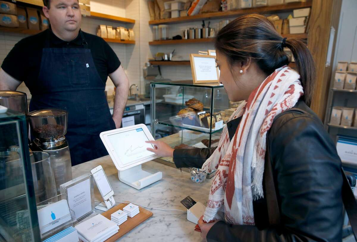 Dianne Francisco pays for her order with a credit card at Blue Bottle Coffee at Market and 10th streets in San Francisco, Calif. on Thursday, Feb. 28, 2019. At left, is barista Greg Alfaro. The cafe inside the Twitter headquarters building is one of a handful of Blue Bottle stores that will go cashless for a trial period beginning March 11.