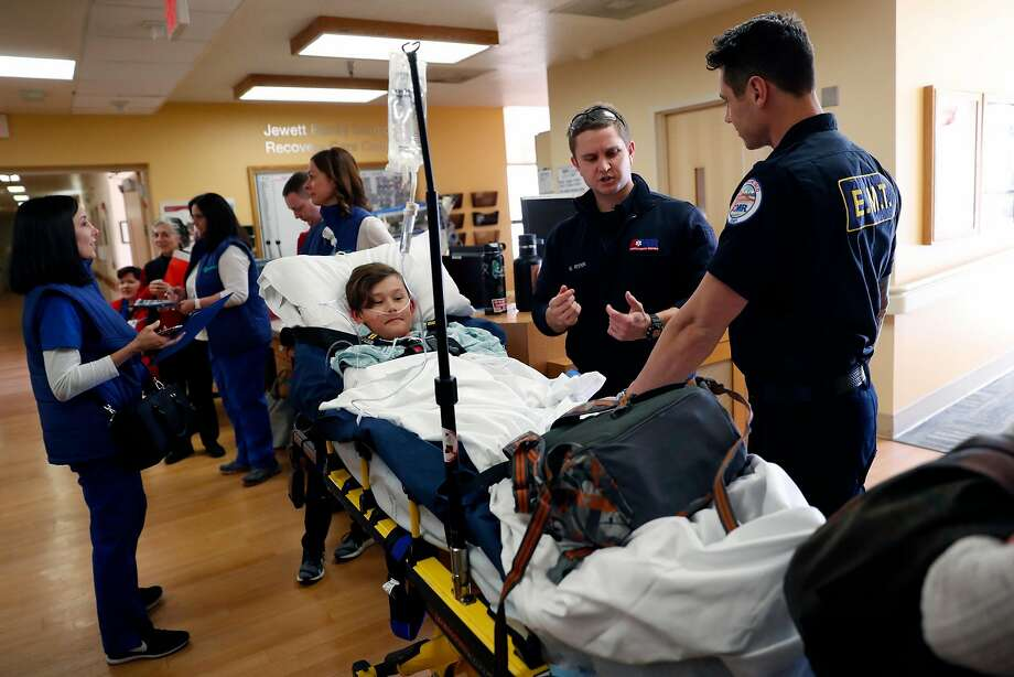 Jinoo Choi, 10, portrays a pediatric patient as  Matt Ryan and Cameron Fletcher practice moving patients. Photo: Photos By Scott Strazzante / The Chronicle