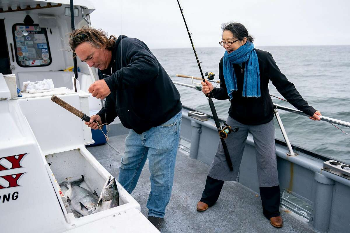 From left: John Dresser using a priest to kill the Chinook Salmon after Mariko Grady reeled the fish into the Whacky Jacky fishing boat on Tuesday, Sept. 18, 2018, off the coast of San Francisco, Calif.