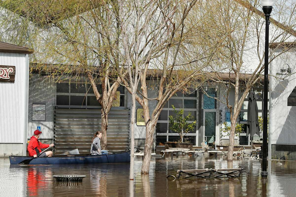 Canoers check out the flooding near The Farmer's Wife cafe at The Barlow in Sebastopol, Calif., on Thursday, February 28, 2019.