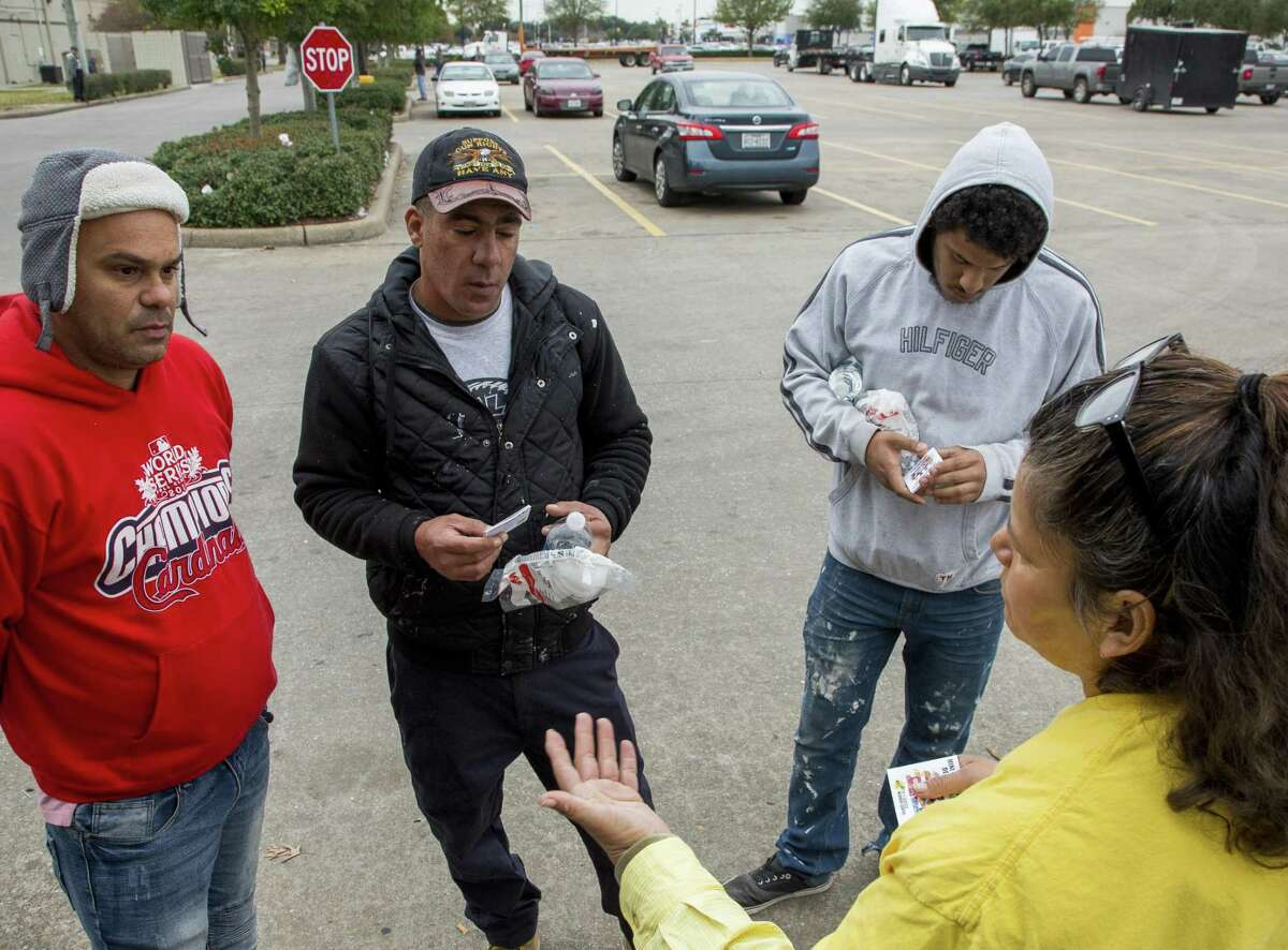 Elvia Escobar, right, with Fe y Justicia Worker Center, talks to Alejandro Lopez Gonzalez, left to right, Javier Molerio, and Santos Ortiz about their rights as day laborers Wednesday, Dec. 12, 2018, in Houston.