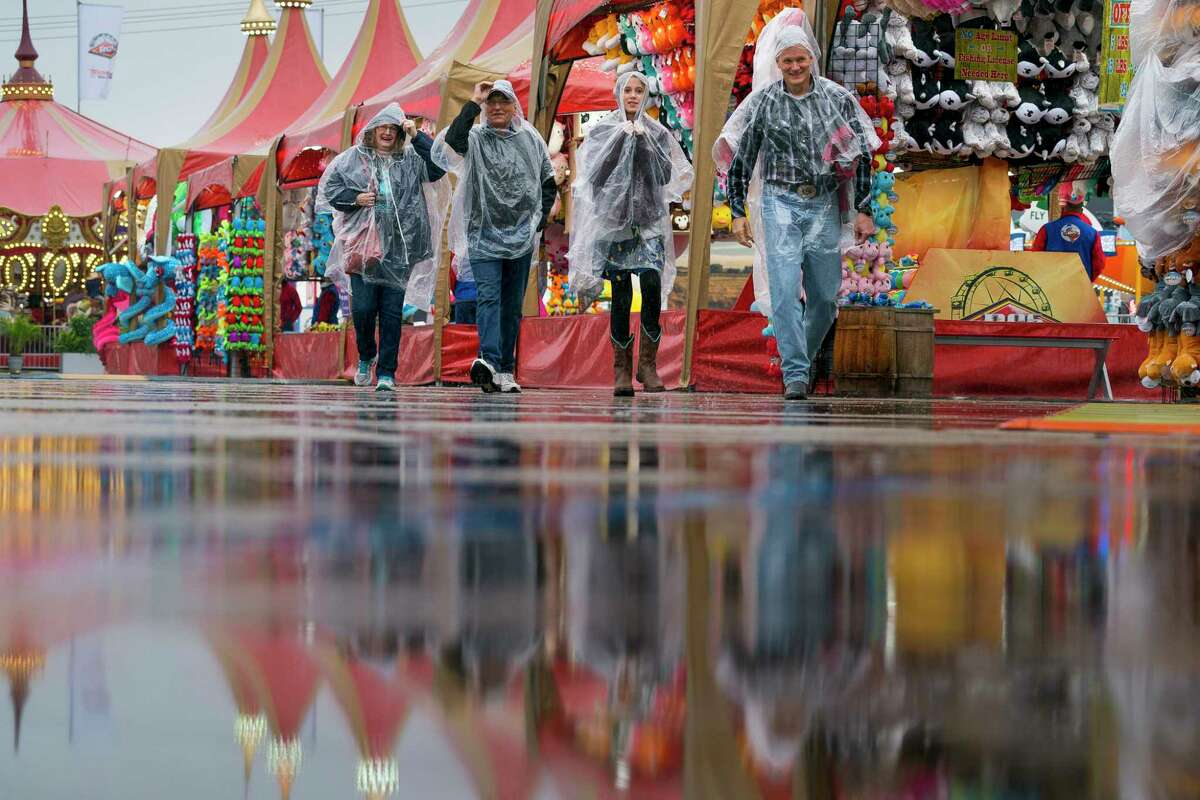 People navigate the carnival at the Houston Livestock Show and Rodeo on a rainy Thursday, Feb. 28, 2019.