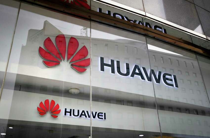 FILE - In this Jan. 29, 2019, file photo, the logos of Huawei are displayed at its retail shop window reflecting the Ministry of Foreign Affairs office in Beijing. Security experts say the U.S. government is likely exaggerating the threat it says the Chinese telecommunications giant Huawei poses to the world?s next-generation wireless networks. Critics say the U.S. case is short on specifics and glosses over the fact that China doesn?t need secret access to Huawei routers to infiltrate global networks. (AP Photo/Andy Wong, File)