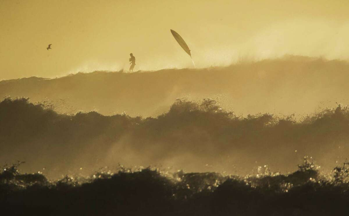 A man stands on a paddleboard while a surfer loses his surfboard at Mavericks Beach, where waves were 20-30 feet high on Wednesday, Dec. 19, 2018, in Half Moon Bay, Calif.