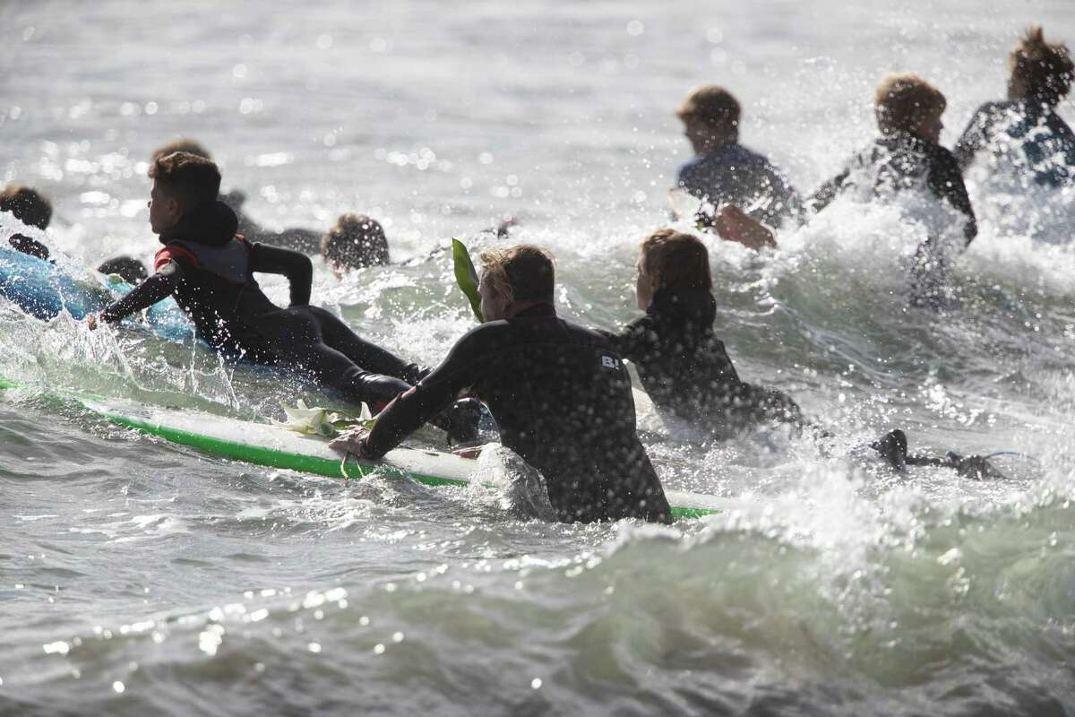Surfers heads out to form a circle at the opening ceremony for the Mavericks big-wave surf contest on Friday, Oct. 26, 2018, in Half Moon Bay, Calif.